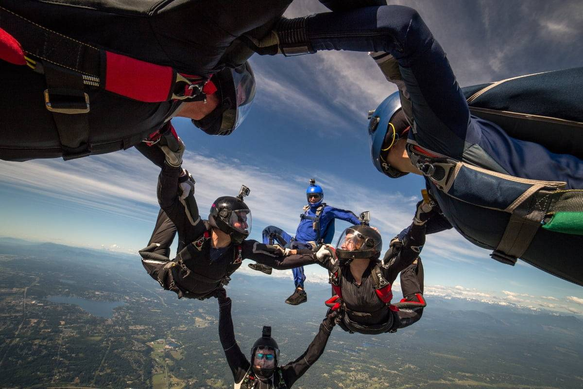 Four experienced skydivers in formation during free fall with one solo skydiver in blue in the background.