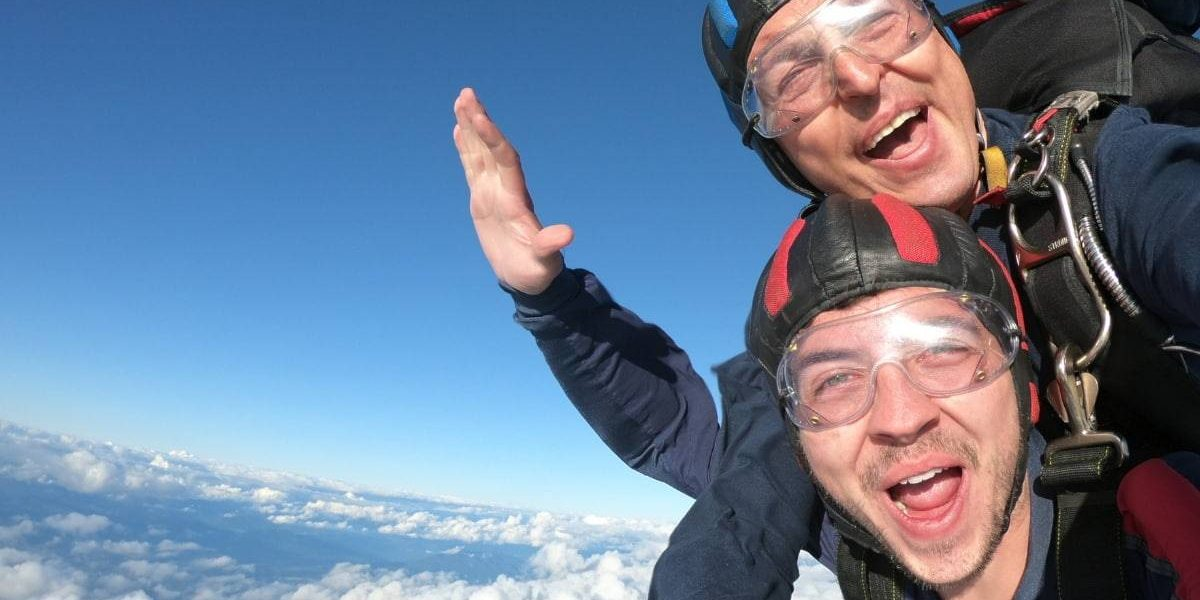 """Young, male, tandem student making a """"woohoo"""" face with while clouds below him."""