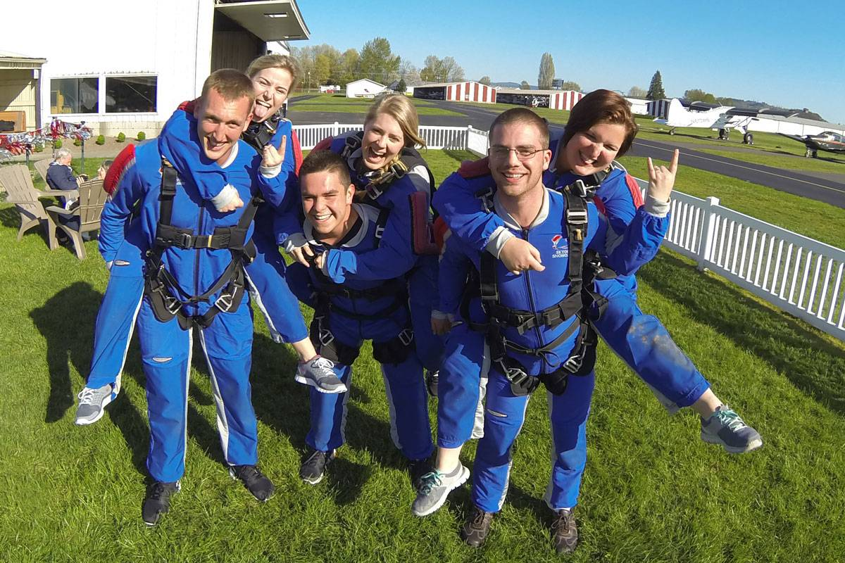 Six young tandem students wearing all blue exited to tandem skydive.