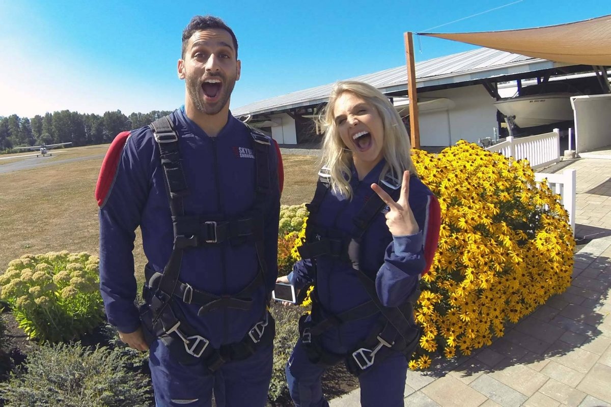 Female with blond hair and gentle men with beard excited to go skydiving with yellow flowers in the background.