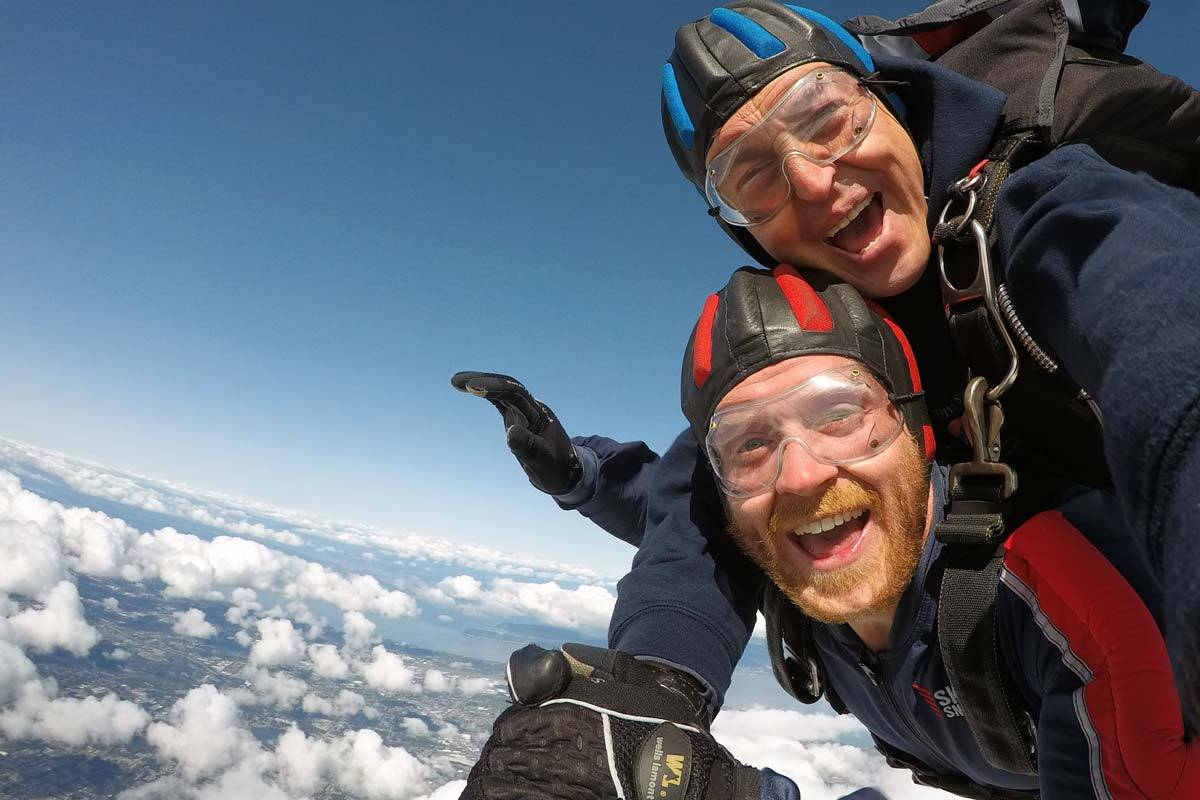 Tandem skydiving student and instructor smiling with white clouds below them