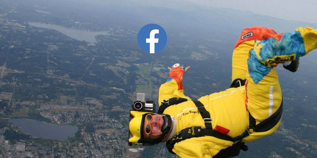 Male in yellow skydiving gear looking at camera and smiling during free fall