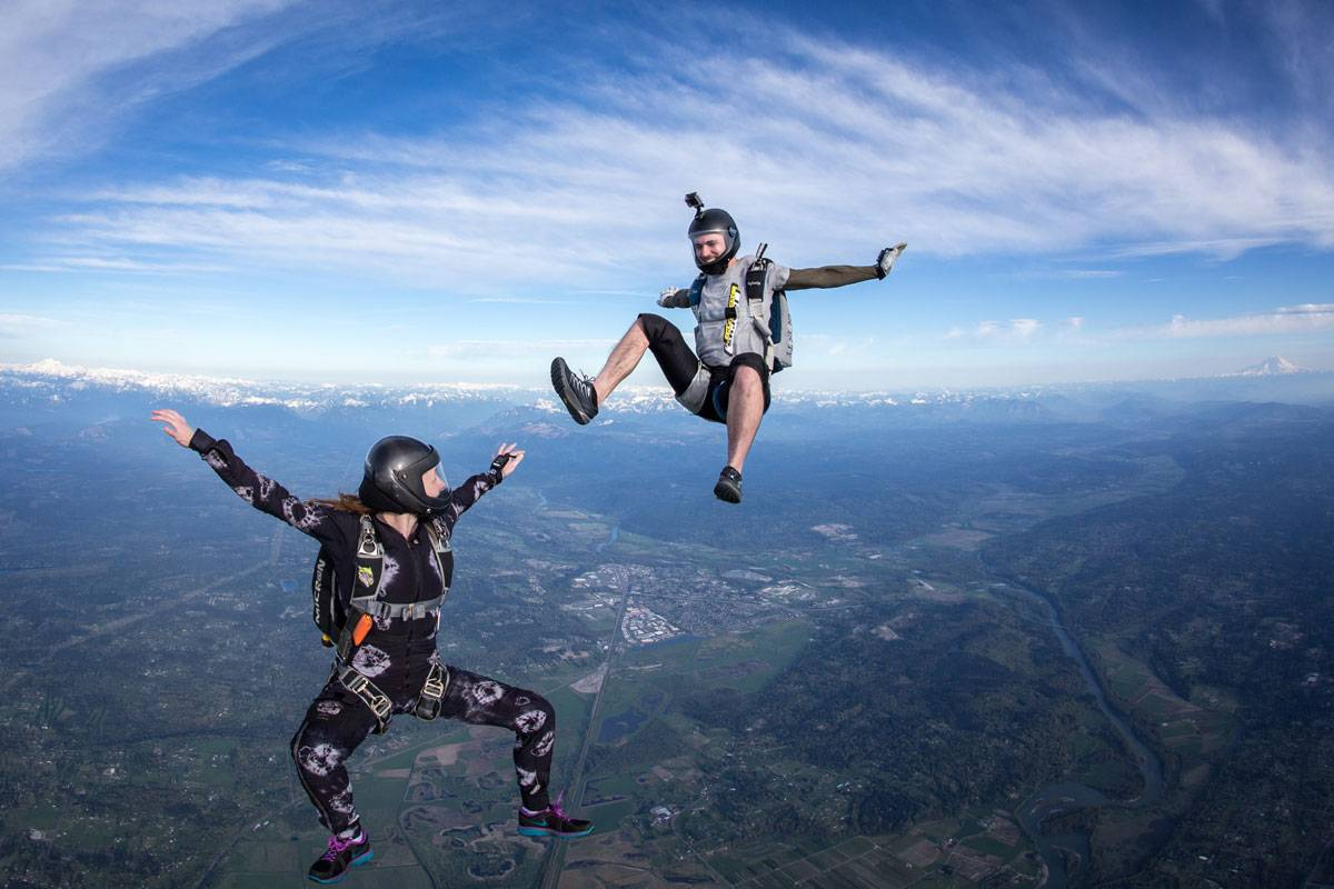 Male and female experienced skydivers in free fall with clear view off the earth below them.