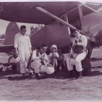 Four gentlemen and child sitting by a plane getting ready to skydive.