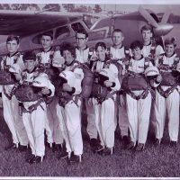 Ten skydivers holding helmets behind older Skydive Snohomish plane.