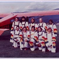 Ten skydivers standing in front of red airplane at Havey Field.