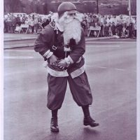 Gentlemen smiling while wearing santa outfit and beard with helmet on.