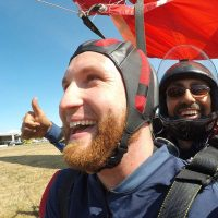 Red headed male tandem student smiling after landing post skydive.