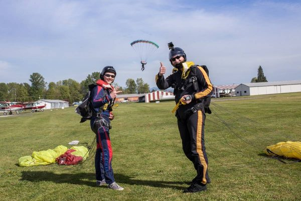 Two jumpers standing with yellow canopies post jump with skydiver close to landing in the background.