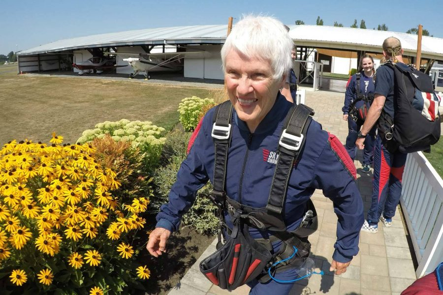 Older female walking past yellow flowers wearing skydiving gear.