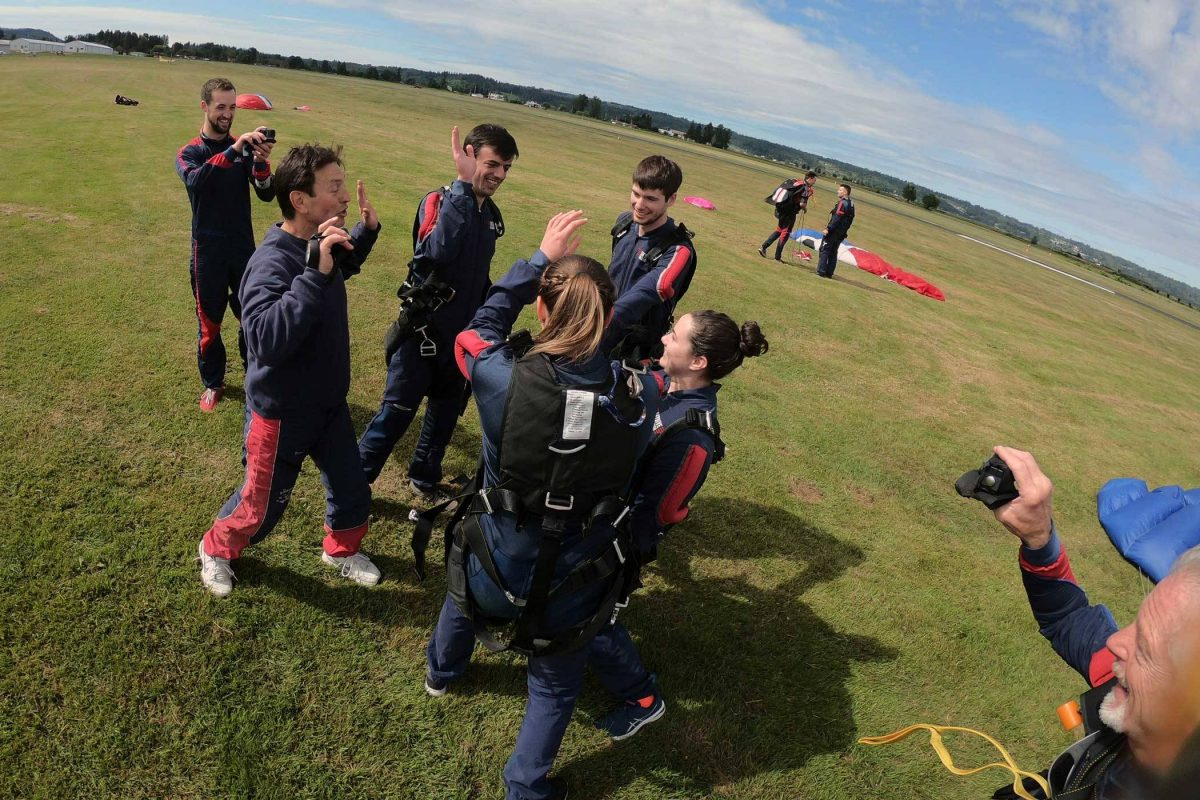 Group of people celebrating post skydive on the green grass landing area.