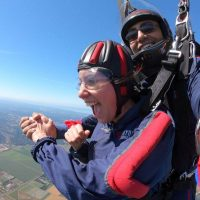 Young women wearing Red and Blue skydiving gear is excited to be in free fall with tandem instructor