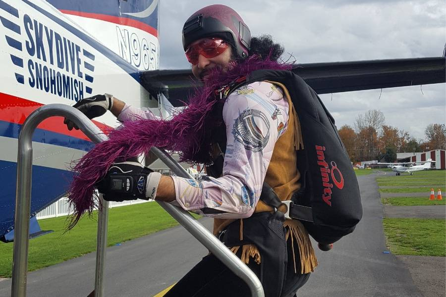 licensed skydiver boards plane weather helmet and purple boa