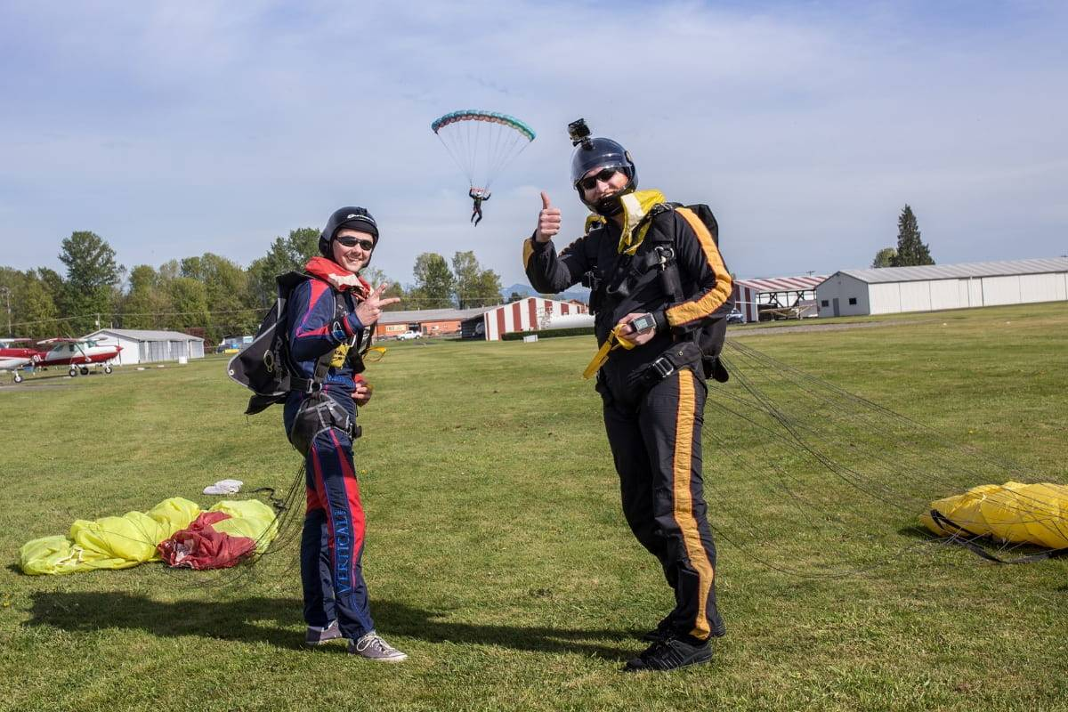 Two skydivers giving thumbs up post skydive with skydiver coming down to land in background.