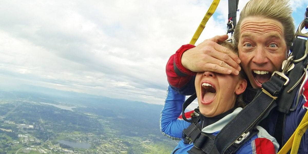 Tandem instructor playfully covering students eyes while skydiving.