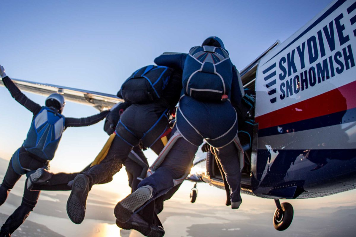 Five experienced skydivers in the process of jumping out of Skydive Snohomish plane while wearing blue gear.