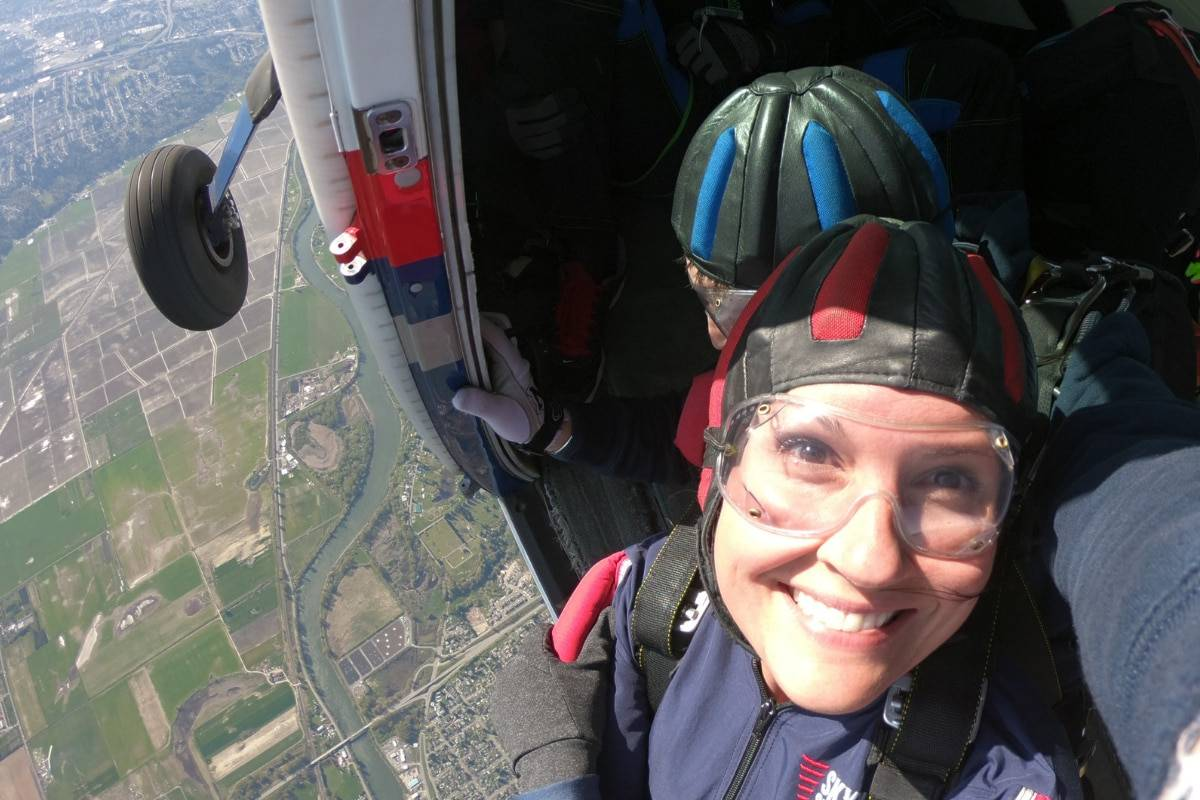 Female tandem skydiver smiling about to take the leap from the airplane.