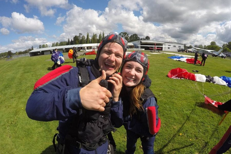 Girl and guy smiling post skydive with Blue, White, Red, and Black canopy in the background.