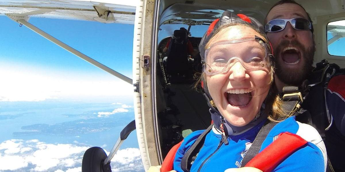 Tandem student wearing blue and red skydiving gear with instructor excited before taking the leap out of the plane.