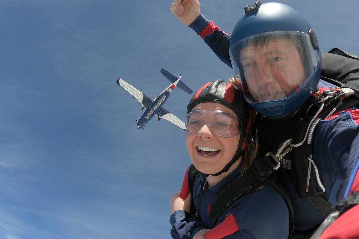 Female tandem student with brown hair smiling while skydiving with Blue, White, and Red airplane above her.
