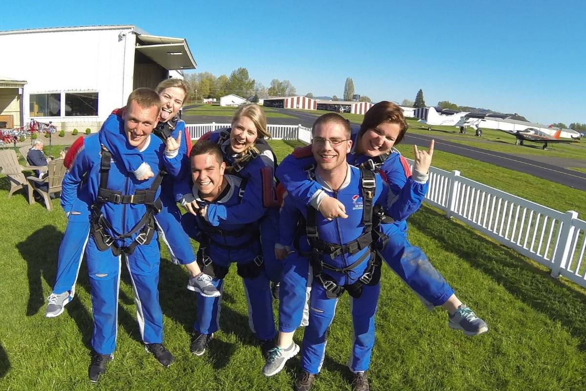 Group of six tandem skydivers wearing all blue gear happily posing outside in grass.