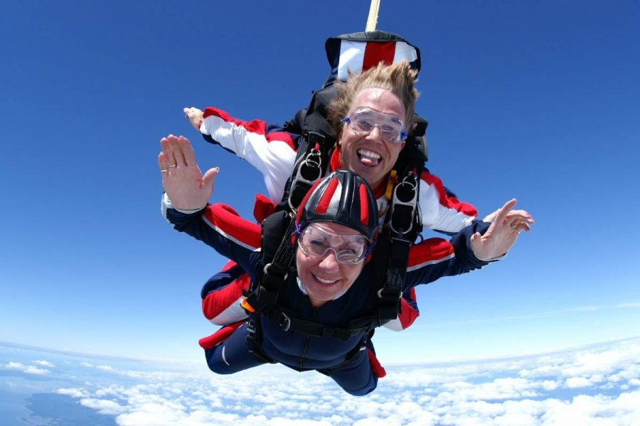 Female tandem student smiling during free fall above white clouds.
