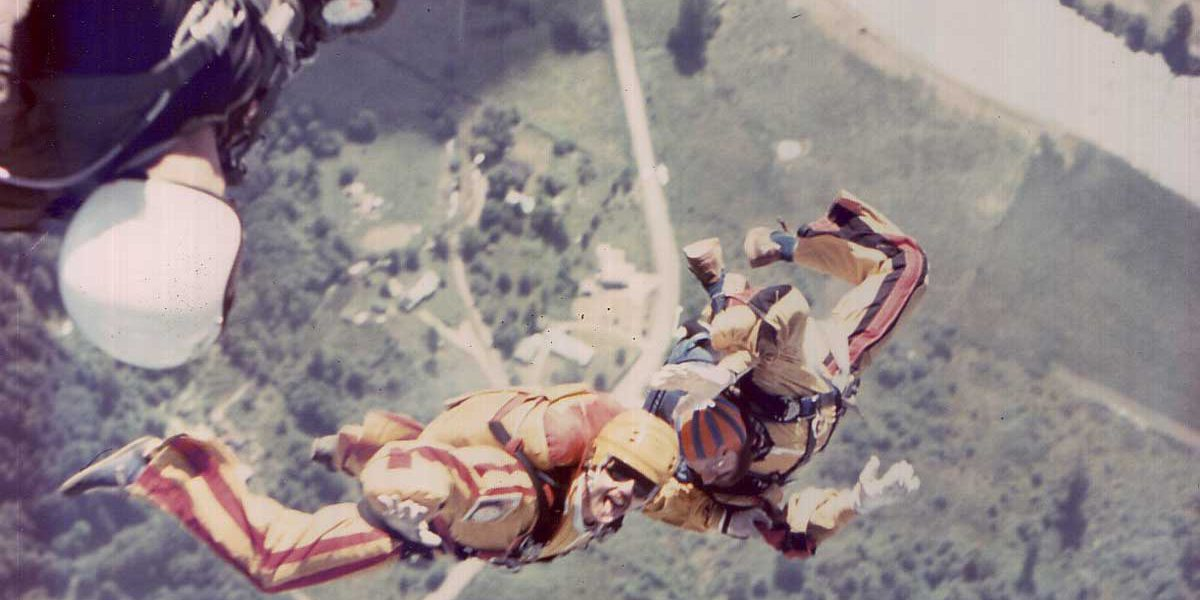 Two experienced skydivers in free fall wearing orange