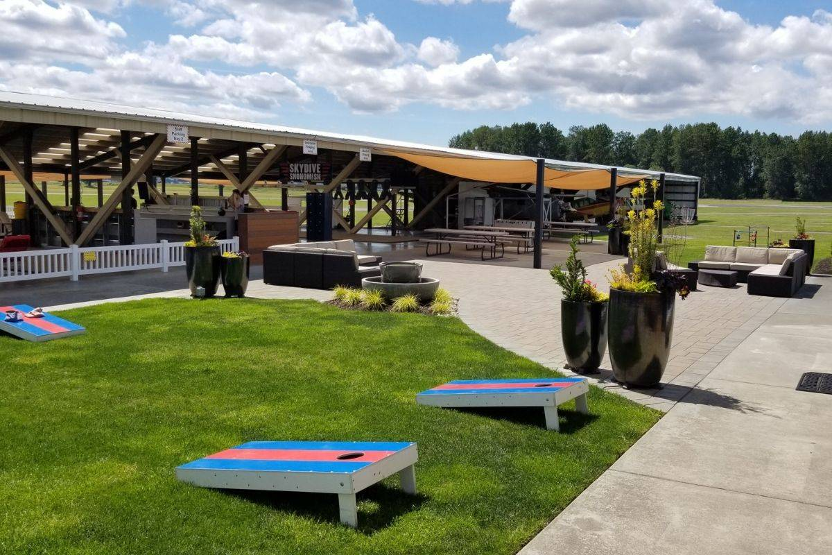 Outside area of Skydive Snohomish with green grass and picnic tables.