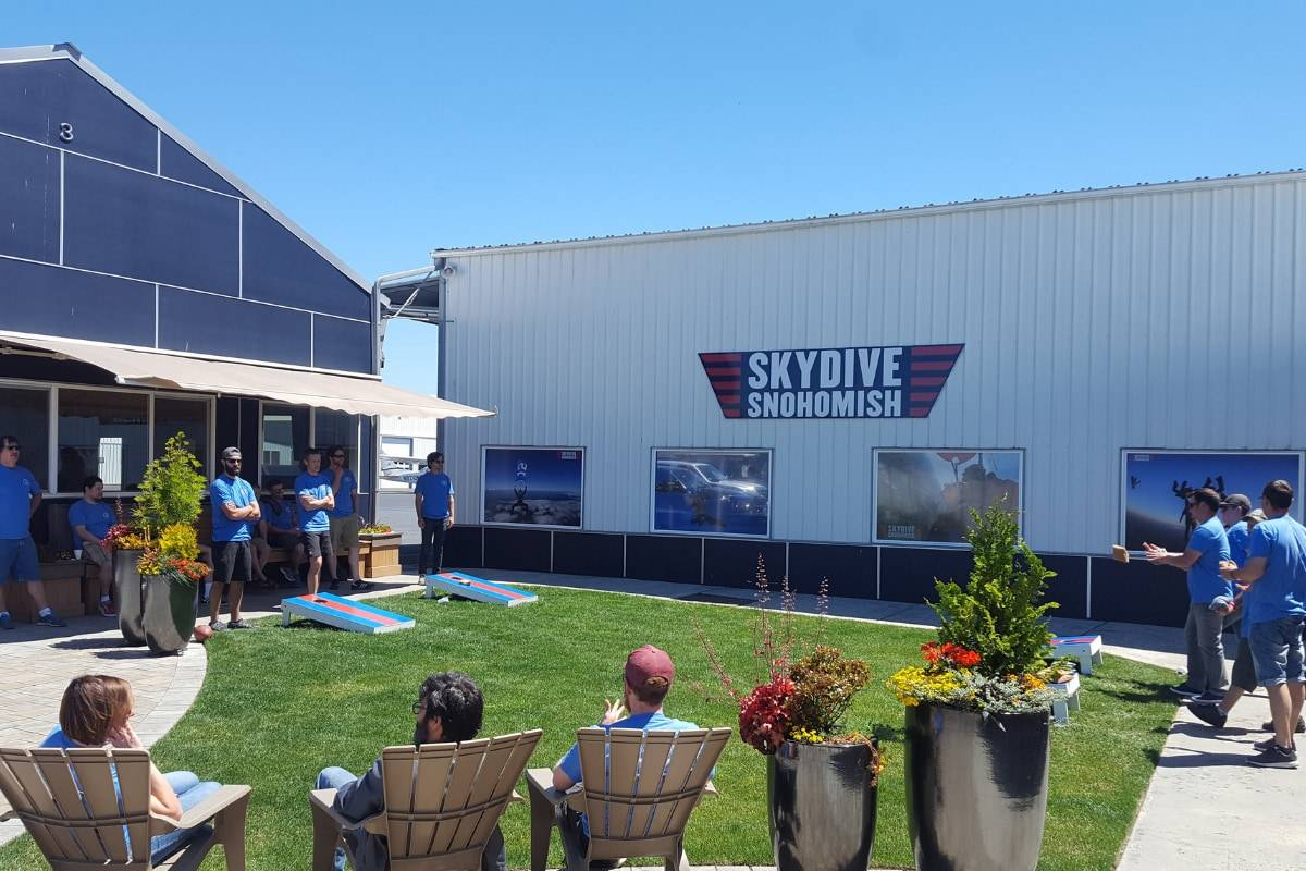 Outside area of Skydive Snohmish with people standing around playing corn hole and sitting in tan chairs.