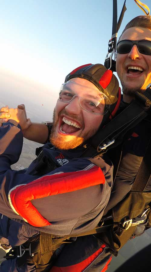 Student and tandem instructor with black sunglasses on in the air smiling.