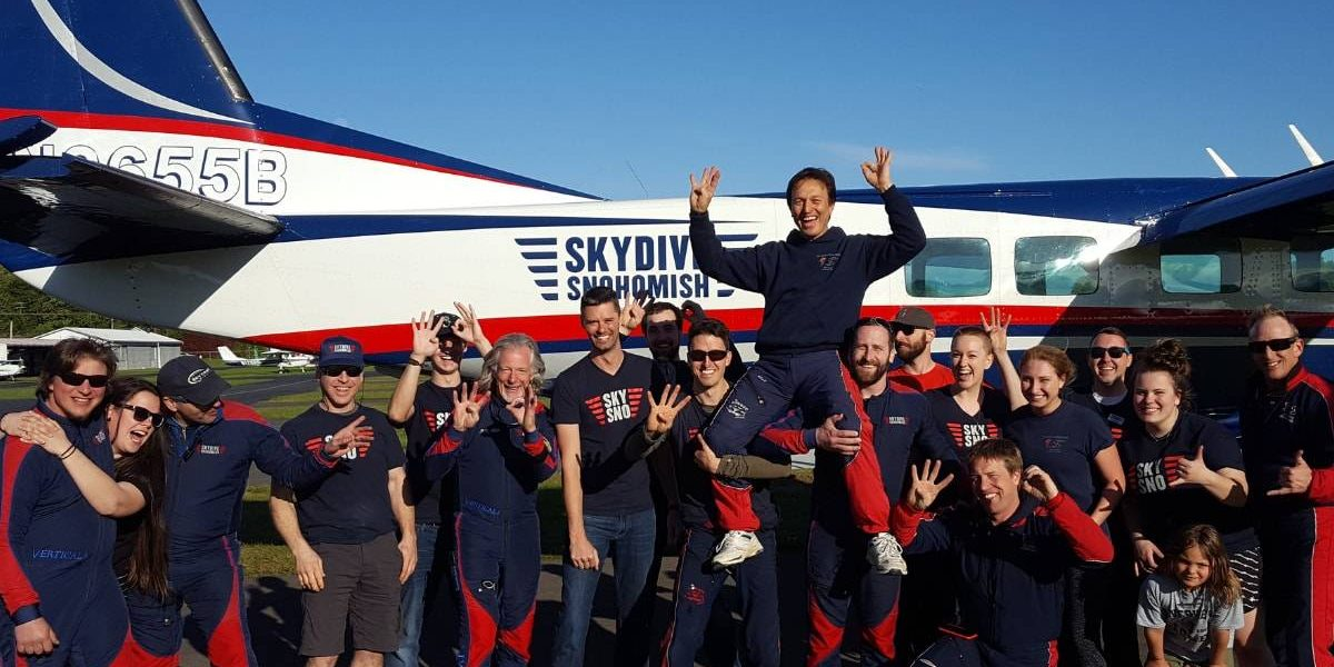 Skydive Snohomish staff posing in front of Red, White, and Blue airplane.