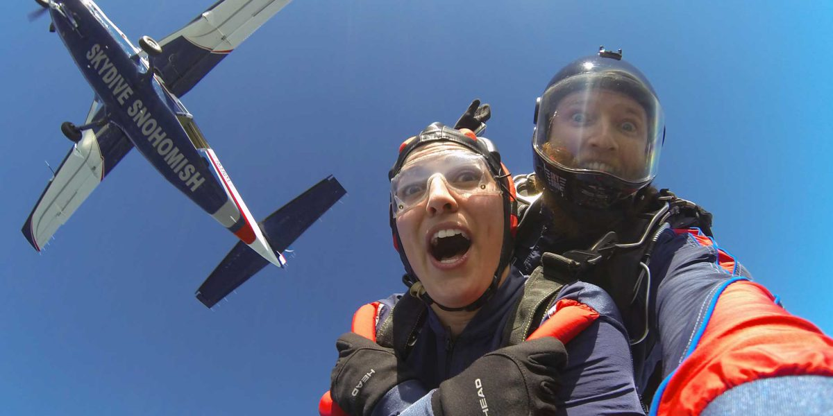 Tandem instructor and female skydiver making excited faces during free fall with blue under belly of plane above them.