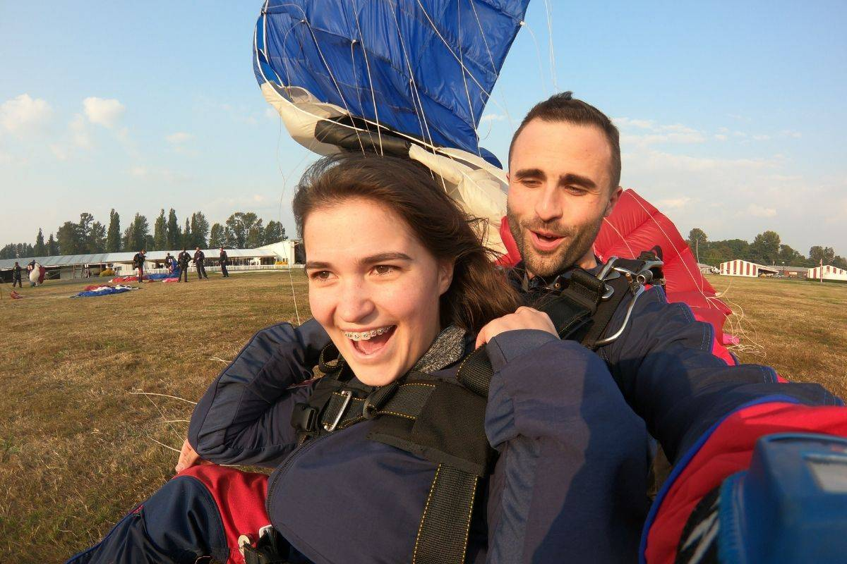 Young female tandem skydiver smiling while landing on the ground with instructor