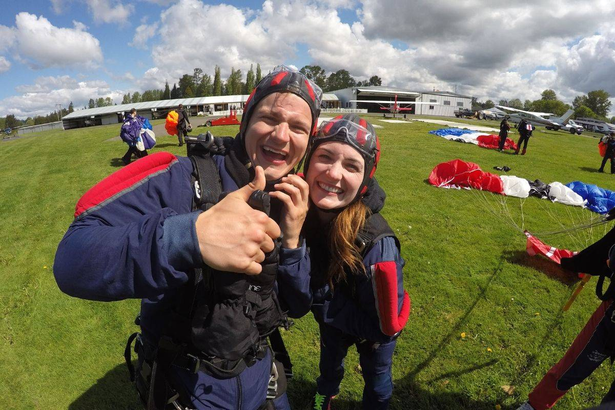 Young male and female smiling while male gives thumbs up post skydive