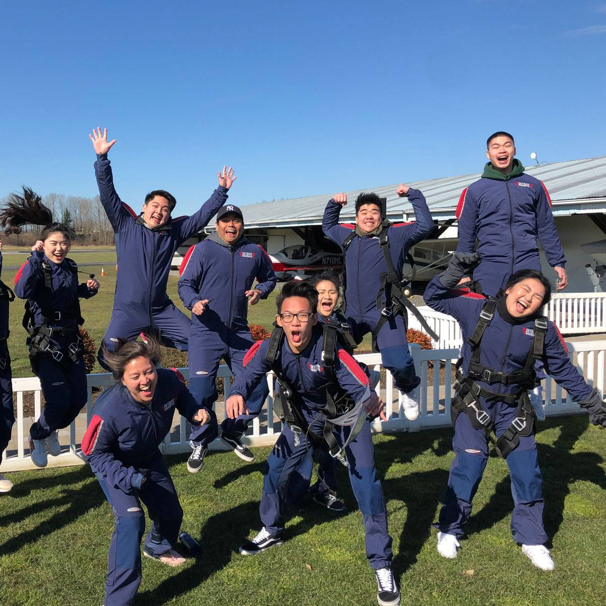 Eleven tandem skydivers jumping in the air excited to go skydiving.