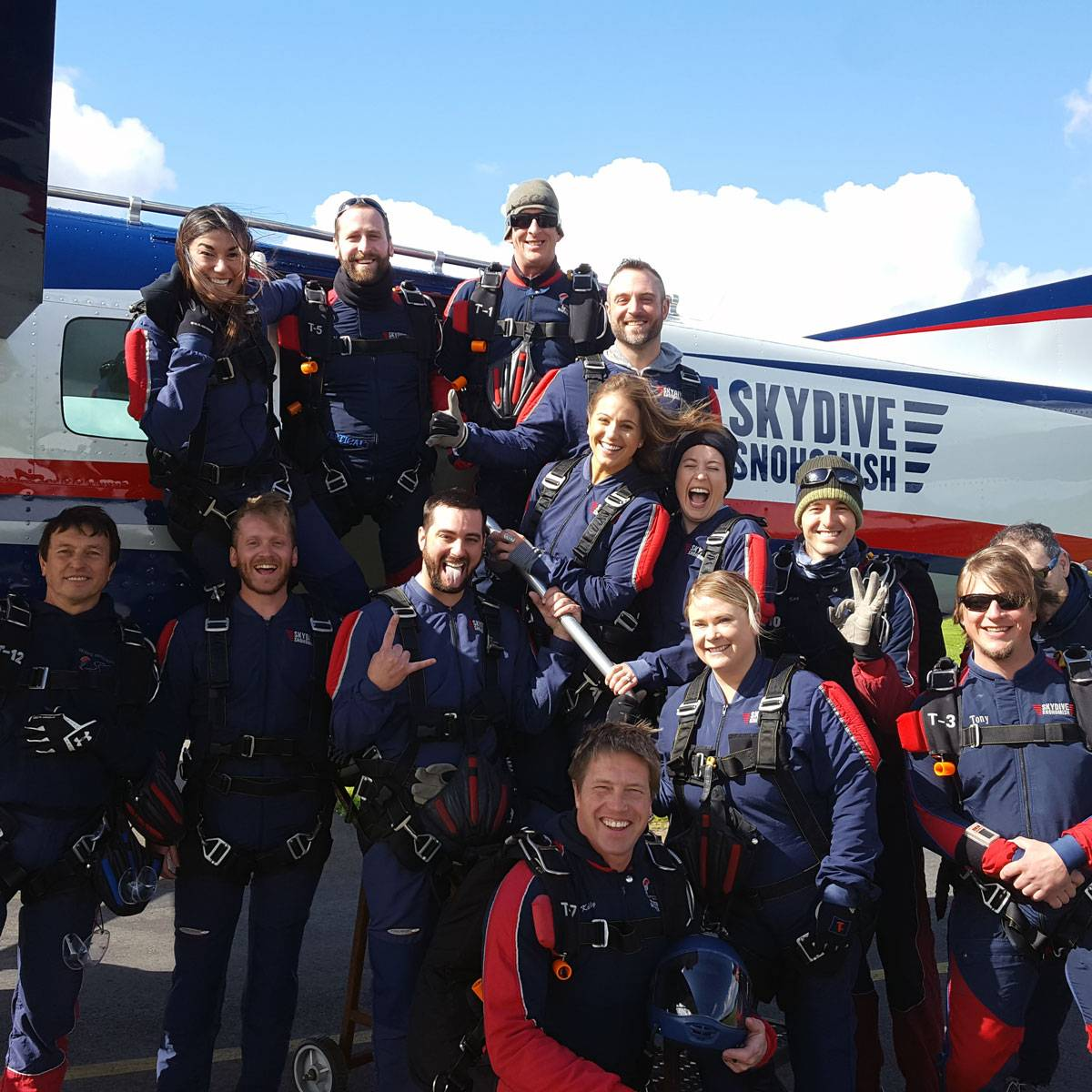 Skydive Snohomish staff smiling in front of Red, White, Blue and Black airplane.