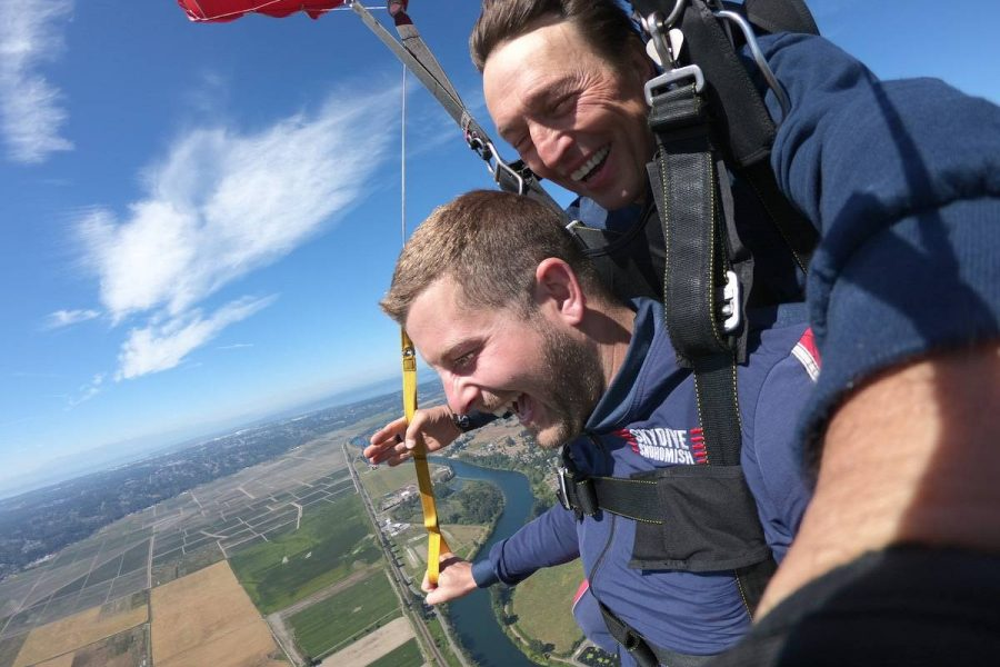 Young male tandem student smiling while skydiving.