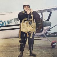 Gentlemen buckling helmet and getting prepared to get on White and Black airplane