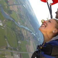 Female tandem skydiver excited floating down towards green land below.