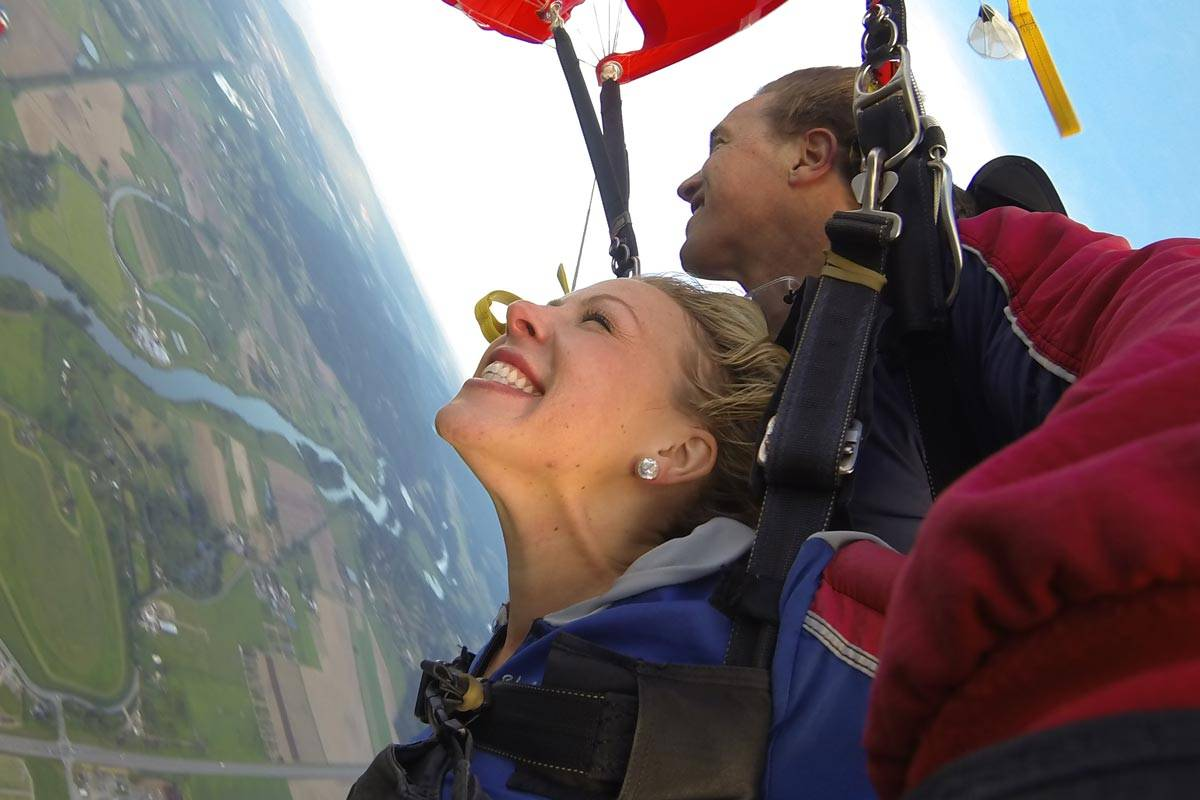 Young female with blond hair happily skydiving.