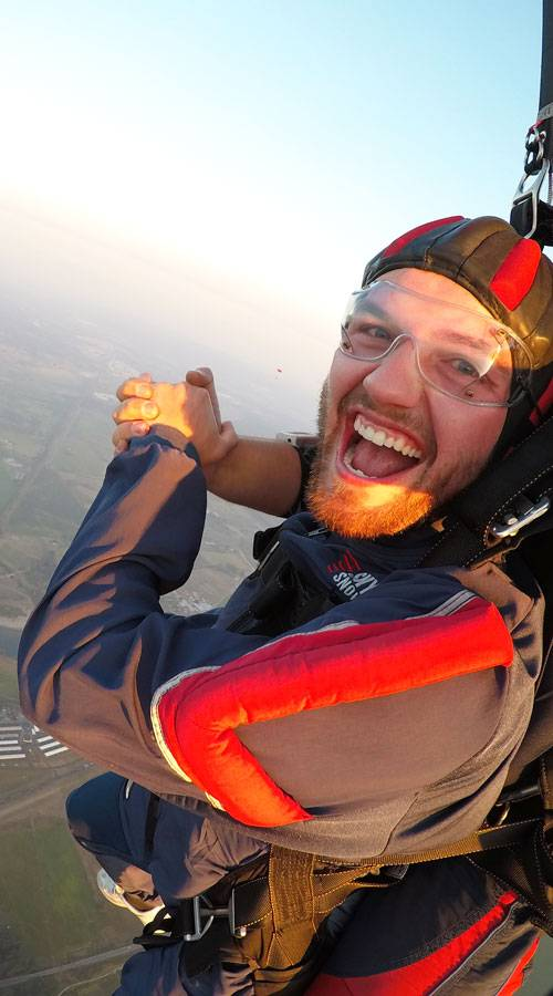 Tandem student smiling while skydiving.