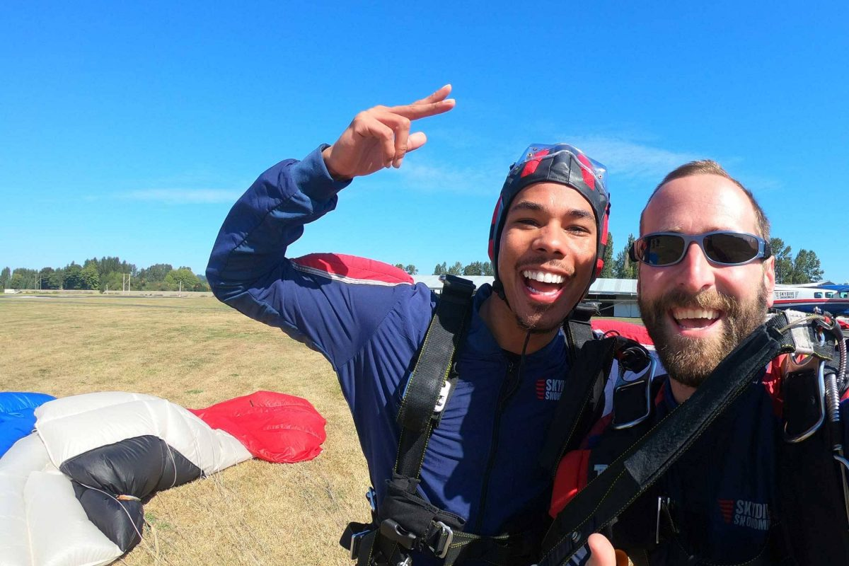Tandem instructor and student excited post skydive with black, white, red, and white canopy in the background.