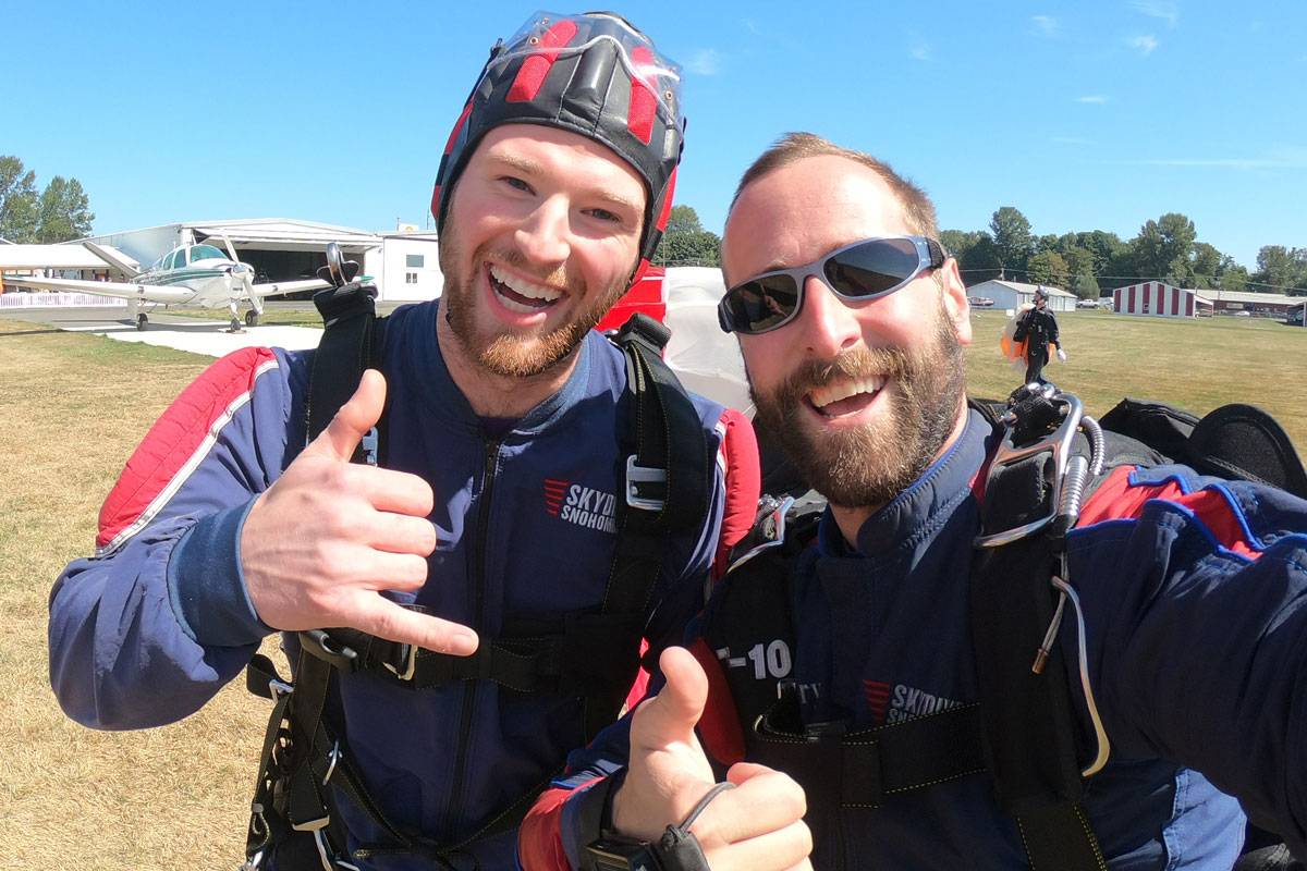 Young male tandem student and instructor giving thumbs up post landing.