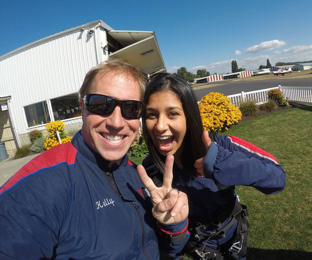 Female tandem skydiver with black hair smiling and giving thumbs up with tandem instructor.