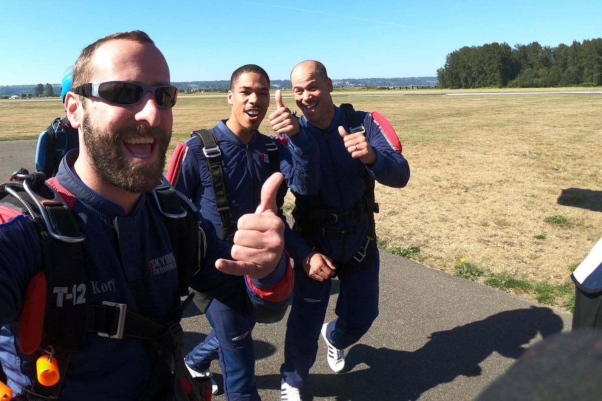 Three male skydivers walking towards airplane to skydive giving thumbs up.