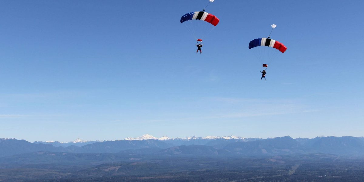 Two experienced skydivers coming towards land with mountains in the back ground and white, blue, red, and black canopies.