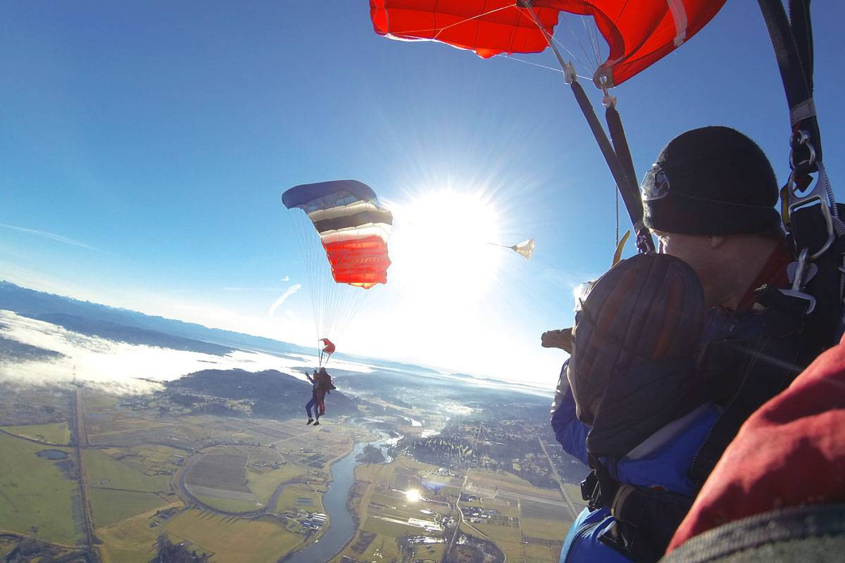 Two sets of tandem skydivers enjoying the view with Red, White, Blue and Black canopies above them.