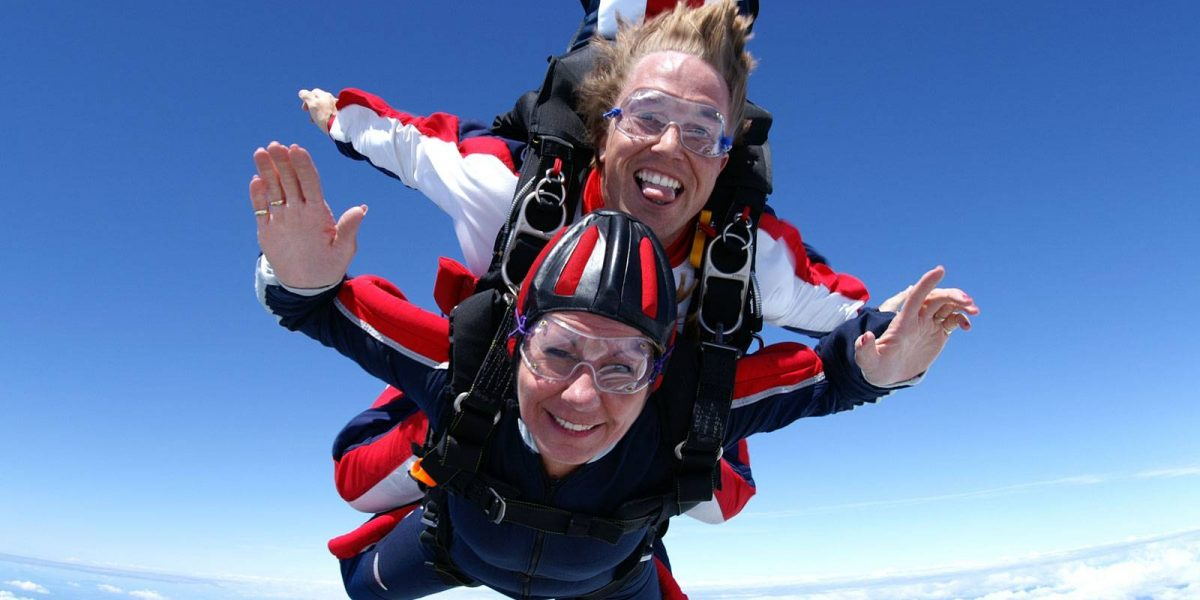 Women and tandem instructor in smiling in free fall surrounded by clouds.