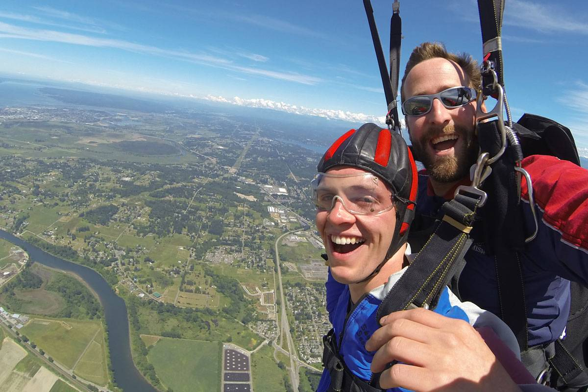 Young male, tandem student and instructor smiling while skydiving.